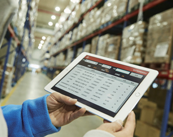 A person holding an iPad with logistics status displayed in the warehouse